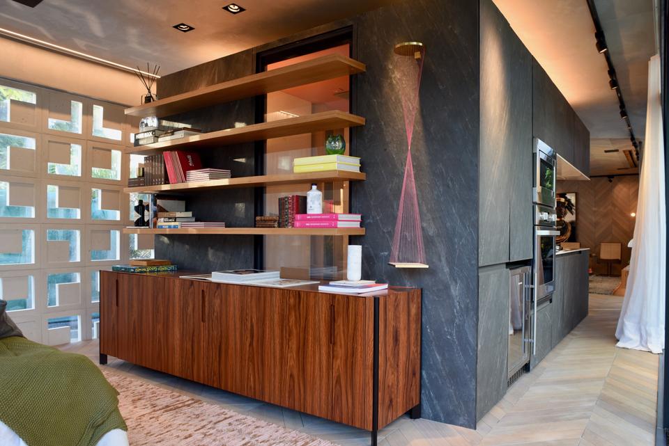 Feito em drywall, o volume central triangular sustenta a estante do quarto de um lado e abriga, nas demais faces, o banheiro e a cozinha do loft