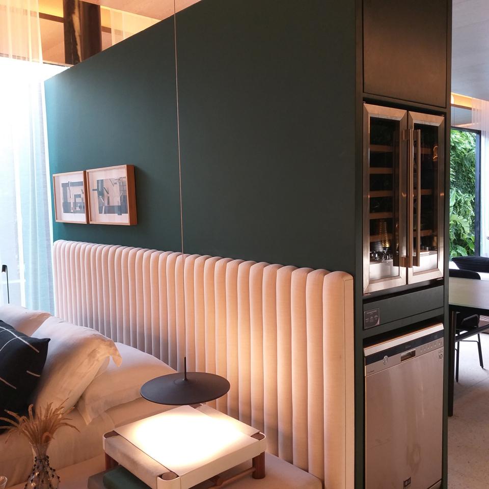 Com função dupla, a parede drywall separa a sala do quarto e embute eletrodomésticos da cozinha integrada